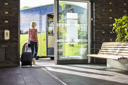 baggage: Young woman at a terminal walks with a wheeled suitcase onto a bus. Traveling with public transport. Stock Photo
