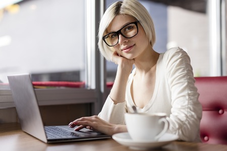 using computer: Smiling woman with laptop computer drinking coffee and doing business or study in a cafe. Stock Photo