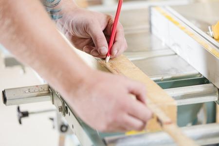伝統: 職人は、木の板の長さを測定します。鋸で挽く前に鉛筆で線を作る。 写真素材