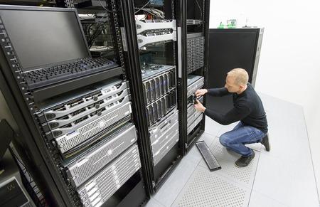 datacenter: It engineer or technician maintaning storage area network SAN in data rack. Shot in datacenter.