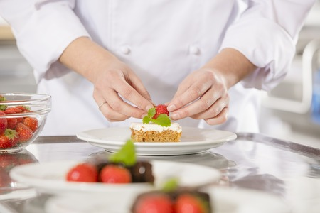 chef kitchen: Close-up of a professional female chef who decorates dessert cake with strawberry and lemon leaf. Large industry kitchen.