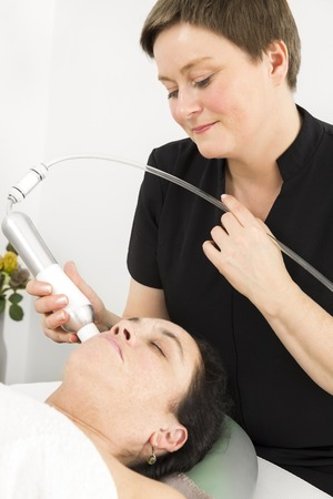 Close up of a client lies with closed eyes for a diamond grinding, peeling, skin lift and drainage at a beauty and spa salon