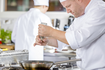 Chef and his assistant prepares beef steak dish in a pan at a professional kitchen. Gourmet restaurant or hotel.