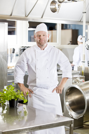 chef kitchen: Portrait of a confindent and smiling male chef standing in the large kitchen with his hands on the hips. Assistant working in the background. Stock Photo