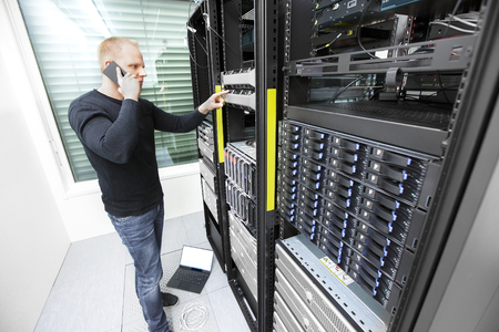 network engineer: It engineer or technician monitors and solving problems with blade servers in data rack. Shot in datacenter.