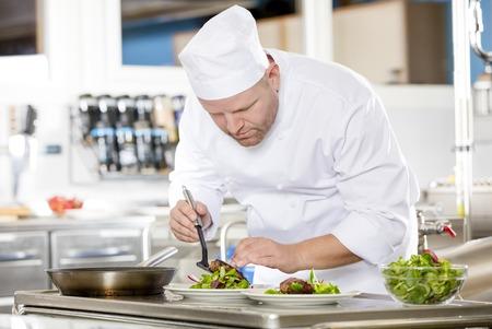cocineros: Cocinero profesional que prepara la carne de vaca plato de carne en una cocina profesional en el restaurante gourmet o un hotel.