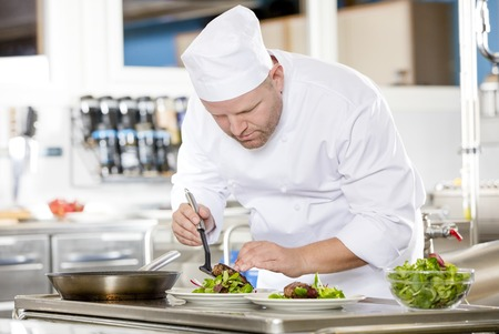 chefs: Professional chef prepares beef meat dish in a professional kitchen at gourmet restaurant or hotel.