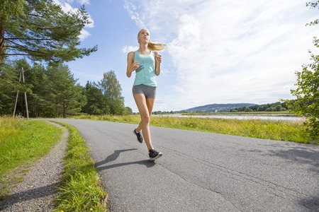 Focused blonde woman trains her stamina when running fast on a road in the forest. Summer evening outdoor.