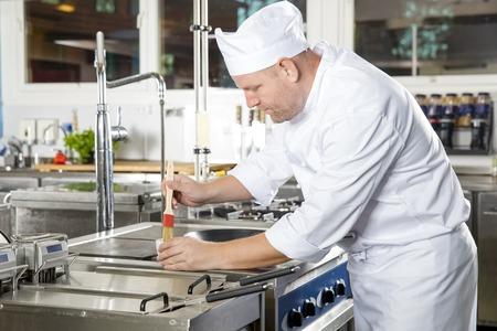 gourmet kitchen: Chef prepares beef steak dish using brush in a professional kitchen. Gourmet restaurant or hotel.