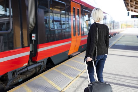 public transport: Young woman at a train terminal walks with a wheeled suitcase to a train. Traveling with public transport.
