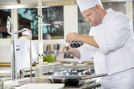gourmet kitchen: Chef and his assistant prepares beef steak dish in a pan at a professional kitchen. Gourmet restaurant or hotel.