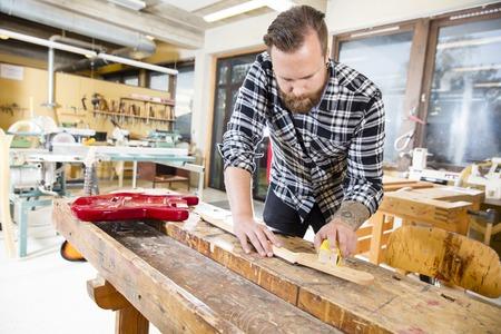carpintero: Artesano usando papel de lija en un cuello de la guitarra en un taller de madera. Hombre de trabajo duro con el tatuaje y la barba se trabaja con instrumentos musicales. Foto de archivo