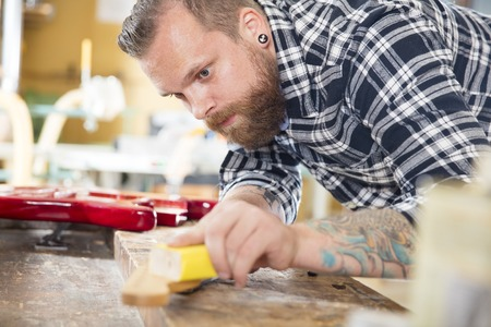 carpenter: Craftsman using sanding paper on a guitar neck in a workshop for wood. Hard working man with tattoo and beard working with musical instruments.