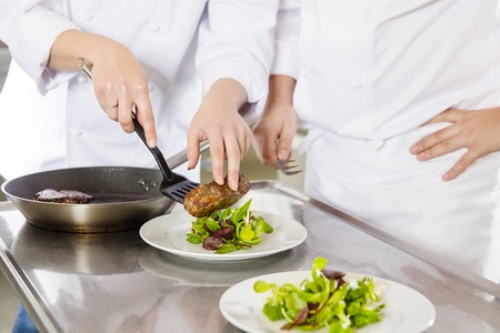 plates of food: Chef and his assistant prepare meat dish with fresh salad in a professional kitchen at restaurant or hotel. Stock Photo