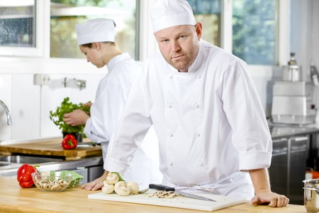 chef: Portrait of a professional male chef standing in the large kitchen. Female assistant or chef working in the background.