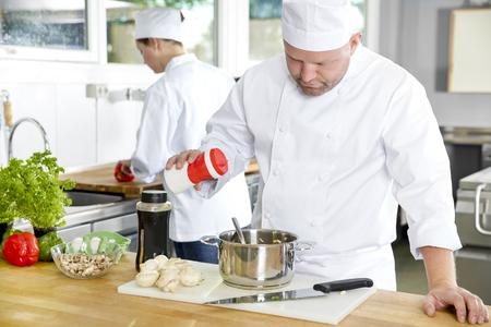 cocina saludable: Cocinero profesional agregar sal en la comida en una cocina industrial en hotel o restaurante. Assistant o chef trabajando en segundo plano.