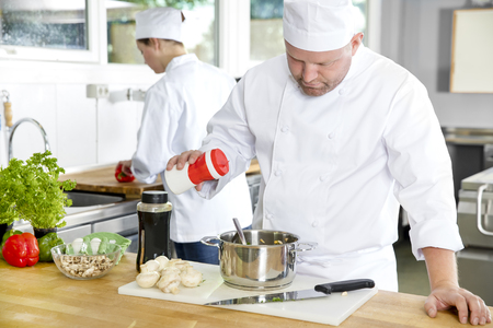 healthy cooking: Professional chef add salt in food at a industrial kitchen in hotel or restaurant. Assistant or chef working in the background.