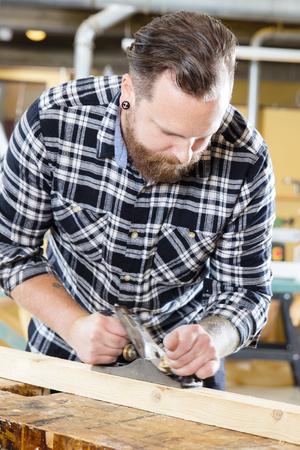 trabajo manual: artesano trabajando duro trabaja con el plano en un taller de carpintería. Handworker con el tatuaje y la barba. desenfoque de movimiento en la cepilladora.
