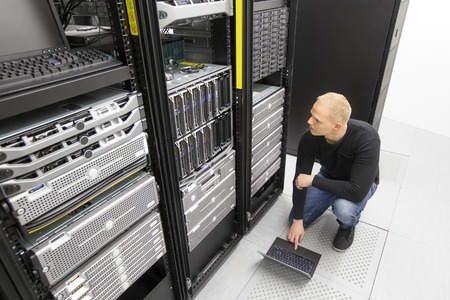 It engineer or technician monitors blade servers in data rack. Working in datacenter.