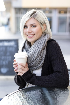 people sitting: Smilng beautiful woman drinks coffee outdoor at a cafe in the city.