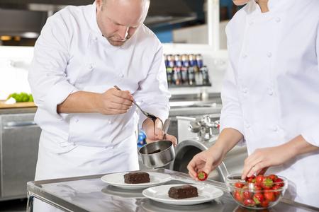postres: Primer plano de chefs profesionales que decora la torta de postre con fresas y salsa de chocolate. Amplia cocina industria. Foto de archivo