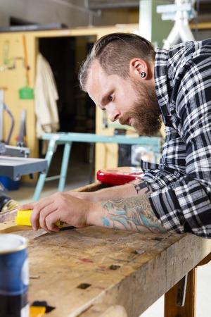planos electricos: Carpintero que usa papel de lija en un cuello de la guitarra en un taller de madera. Hombre de trabajo duro con el tatuaje y la barba se trabaja con instrumentos musicales. Foto de archivo