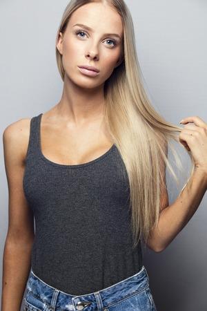 Mooi en natuurlijk ogende jonge blonde vrouw die haar haren. Natuurlijk en licht geretoucheerd studio foto.