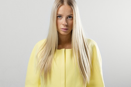 studio photography: Beautiful young blonde woman with yellow fashion design jacket. Scandinavian or nordic contemporary style. Studio photography.