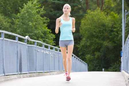 skinny girl: Beautiful young slim blonde woman running or jogging on a bridge. Stamina workout a summer evening.