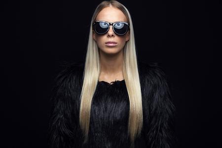 cabello negro: Hermosa mujer de moda joven con el pelo rubio largo y una chaqueta de diseño peludo negro. Niña mirando fresco con los vidrios en el estudio. Fondo negro. Foto de archivo