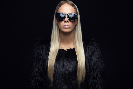 Beautiful young fashion woman with long blonde hair and black furry design jacket. Cool looking girl with glasses in studio. Black background. Standard-Bild
