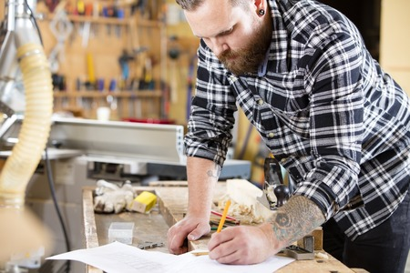 causal clothing: Craftsman looks at drawing in a work shop for wood work and construction. Carpenter designs and plans new work.