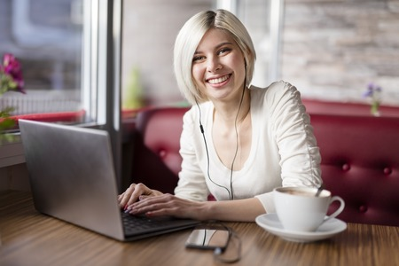 woman smiling: Smiling blonde woman with laptop computer drinking coffee and doing business or study in a cafe.