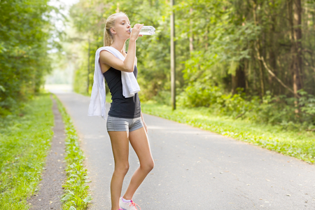 having a break: Blonde woman having a break after jogging outdoor in the forest. Rests and drinking water. Stock Photo