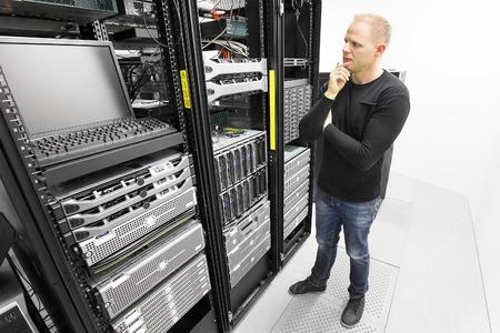 computer centre: Es ingeniero o t�cnico de monitores y de resoluci�n de problemas con los servidores blade en los datos de rack. Apoyo t�cnico en el centro de datos. Foto de archivo