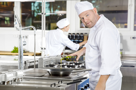 Two chefs working in gourmet restaurant or hotel. Chef pours olive oil in a pan in a professional kitchen.