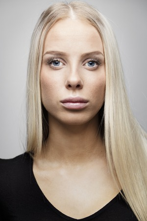 natural looking: Beautiful and natural looking young blonde woman with blonde hair. Natural and light retouched studio potrait.