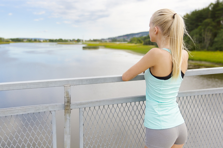 sporty: Beautiful young fit blonde woman taking a break after jogging or running. Standing on a bridge and leaning on the fence while she thinking.