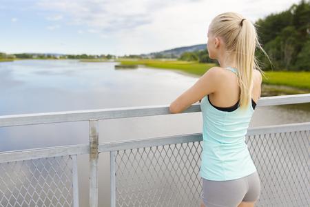 atletismo: joven y bella mujer rubia en forma de tomar un descanso después de trotar o correr. De pie en un puente y apoyado en la baranda, mientras que pensar.
