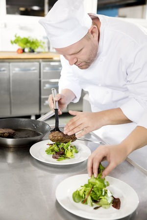 garnish: Chef and his assistant prepare meat dish in a professional kitchen at restaurant or hotel. Stock Photo