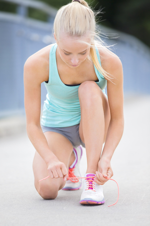 girl shoes: Pretty and slim blonde athletic female runner tying shoelaces outdoor on a bridge. Stock Photo