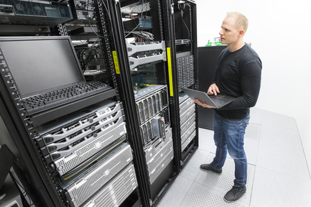 computer center: It professional or technicial consultant monitors blade servers in data rack. Shot in datacenter. Stock Photo