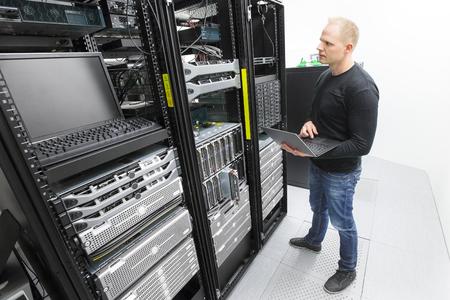 It professional or technicial consultant monitors blade servers in data rack. Shot in datacenter. Foto de archivo