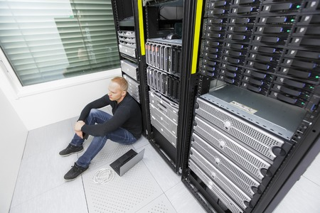 it technician: Exhausted and tired IT engineer or technician with large problems sitting and leaning against data racks in a datacenter.