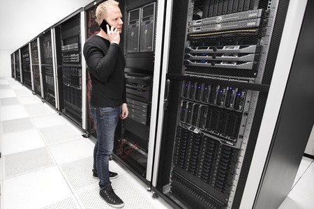 solve problems: IT consultant or engineer work and solve problems in data room. Photo from a large enterprise datacenter. Stock Photo