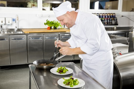gourmet kitchen: Happy professional chef prepares beef meat dish in a professional kitchen at gourmet restaurant or hotel. Stock Photo