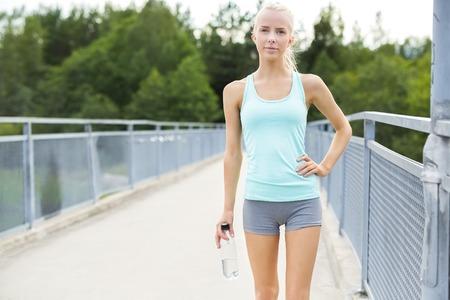 skinny: La mujer rubia joven feliz y en forma tener un descanso después de correr. De pie con la mano en la cadera en un puente.