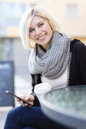 ourdoor: Smiling beautiful woman drinks coffee outdoor at a cafe in the city. Using smartphone. Stock Photo