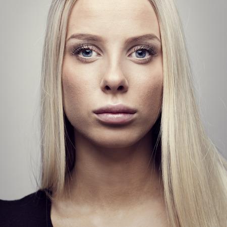 blonde yeux bleus: Fermer portrait d'une belle et naturelle regardant visage jeune femme blonde avec les cheveux blonds. Naturel et lumière retouchés potrait studio.