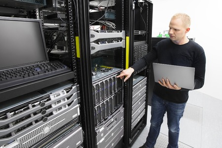 it technician: It engineer or technician monitors blade servers in data rack. Working in datacenter.